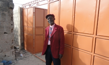 Headmaster Mr. Bangura in front of the new gates
